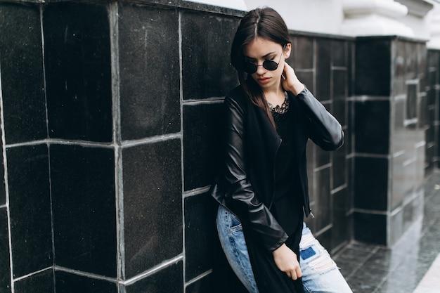 Женщина возле черной стены, касаясь ее шеи