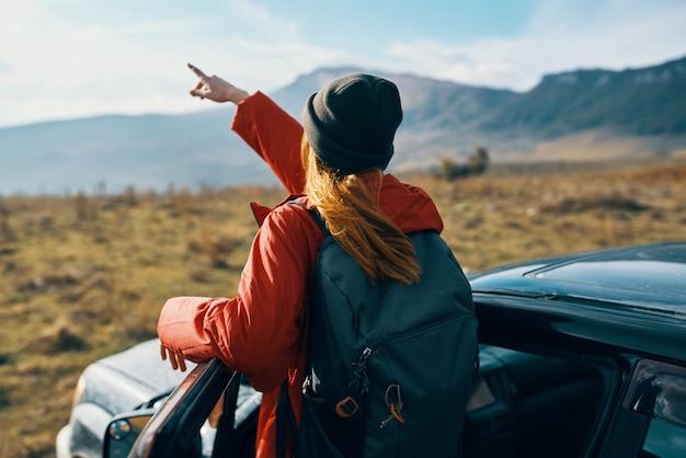 山の秋のバックパック旅行観光で自然に彼女の手で身振りで示す車の近くの女性