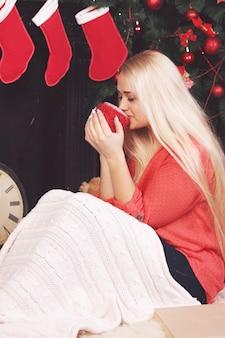 뜨거운 음료를 마시는 크리스마스 트리 근처 여자