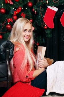 크리스마스 트리 근처 여자는 책을 읽으십시오