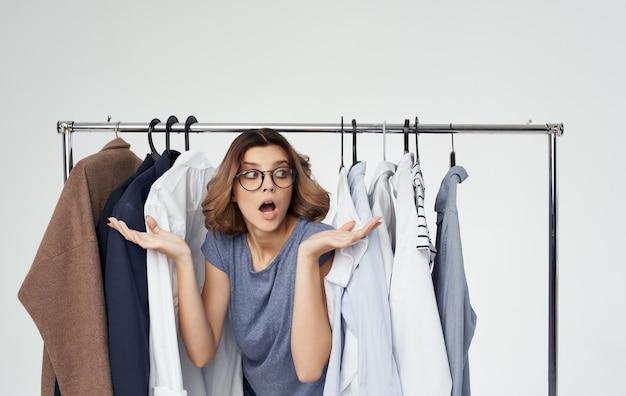 Женщина около одежды на модели стиля моды вешалки.