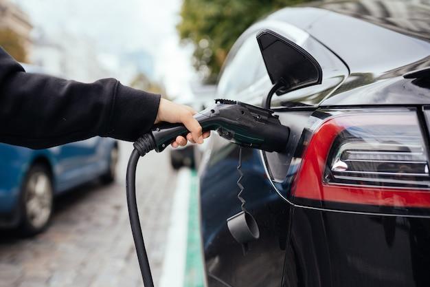 Женщина возле электромобиля. автомобиль заряжен на зарядной станции.