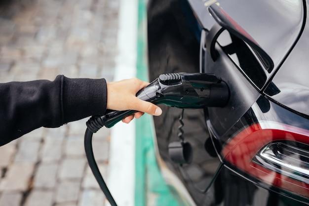 Donna vicino all'auto elettrica. veicolo caricato alla stazione di ricarica.