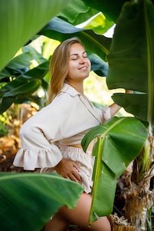 Женщина возле зеленых листьев банановых кустов на природе в парке в тропическом месте, она в бежевой юбке и блузке