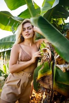 Женщина возле большого зеленого листа бананового дерева на природе в парке. тропические растения