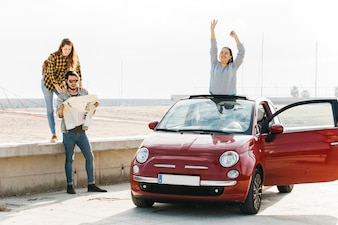 Woman near man looking at map and positive lady leaning out from car near beach