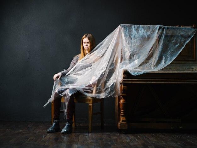 Женщина возле пианино позирует модной музыкой