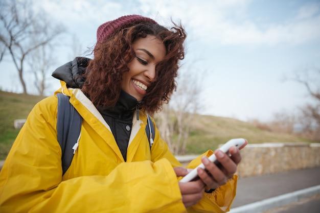Женщина возле дороги с помощью смартфона