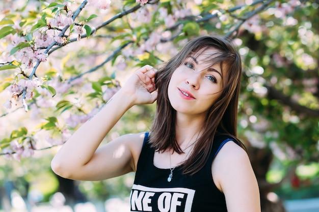사쿠라 피 나무 근처 여자입니다. 피 나무에 소녀입니다. 봄 개념