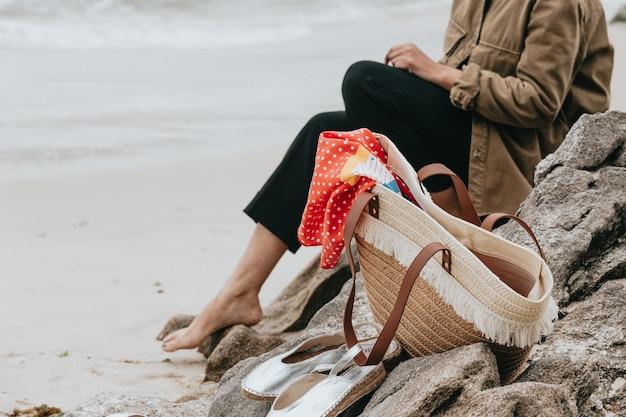 晴れた日のビーチでいくつかのサンダルと夏のバッグの近くの女性