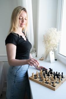 チェス盤の近くの女性。戦略を考えている女性。
