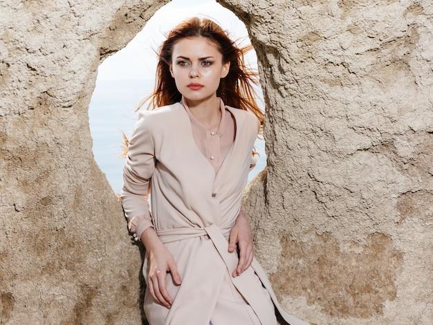 大きな石と軽い服のクロップドビューの穴の近くの女性