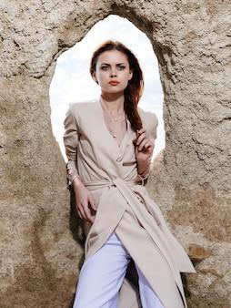 大きな石と軽い服のトリミングされたビューの穴の近くの女性