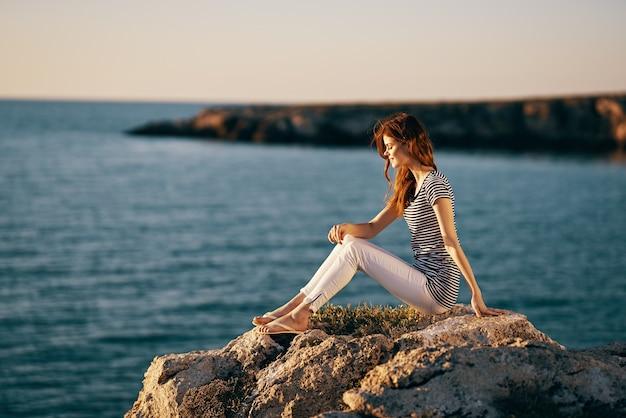 大きな石の海の風景の夕日の海の山の近くの女性