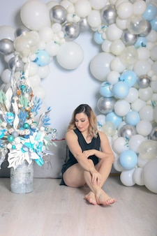 Woman near white christmas decoration with naked legs. sexy girl posing on the floor with naked feet