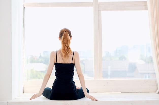 窓の近くの女性ヨガ瞑想リラクゼーション