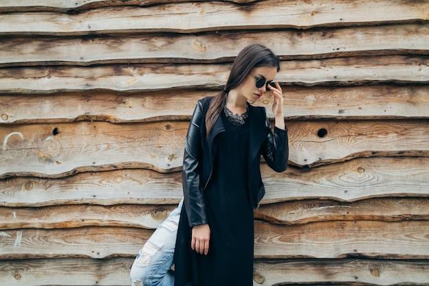 Женщина возле деревянной стены