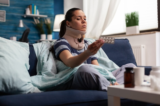 Woman in neck brace suffering from pain on sofa
