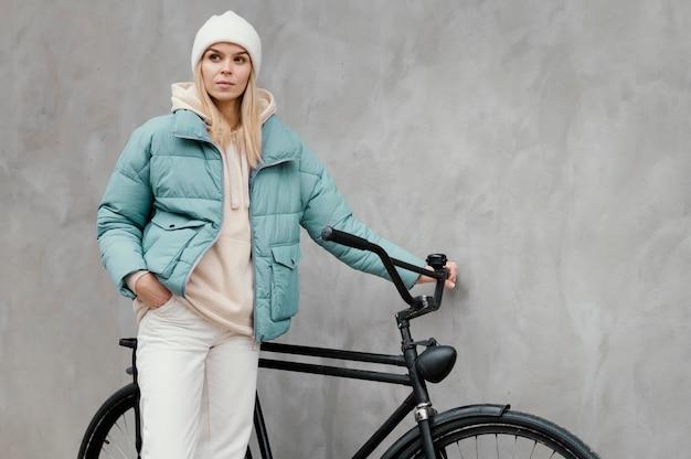 彼女の自転車の横にあり、目をそらしている女性