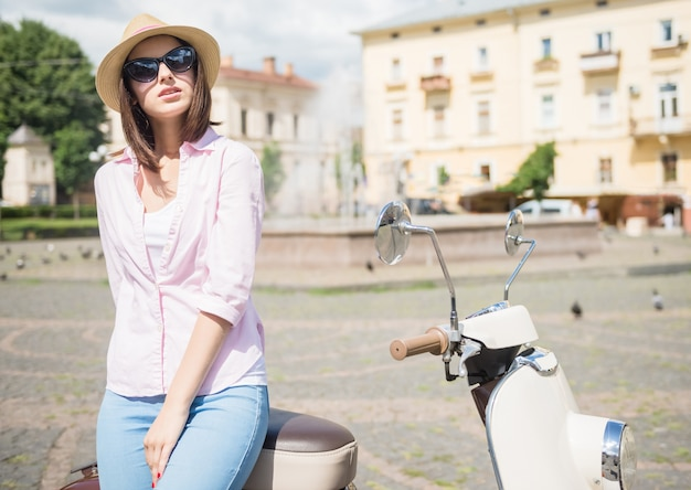 Woman in nifty hat standing near scooter outdoors.