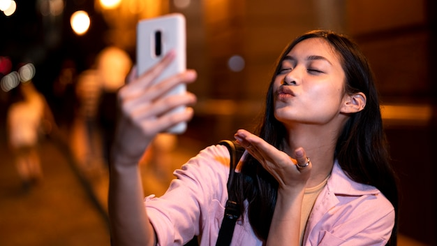 Woman at night in the city lights taking selfie and sending kiss