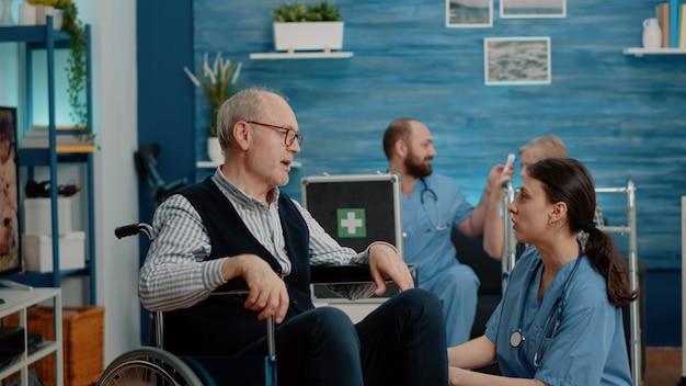 Woman nurse comforting disabled senior man about disease