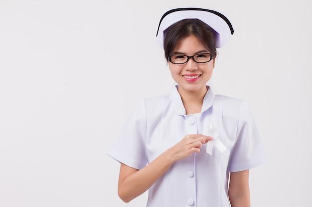 Медсестра женщины держа белый смычок ленты; рак мозга, аллергия, символ осведомленности астмы; концепция белой ленты для рака костей, болезней костей, остеопороза, слепоты, слепых людей, осведомленности о грыже