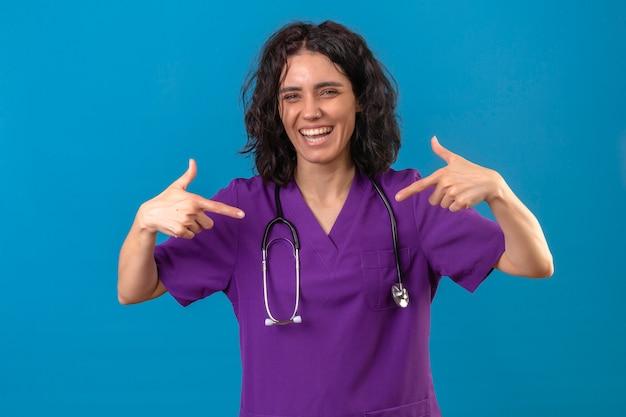 Женщина-медсестра в медицинской форме и стетоскопе, указывая на себя большими пальцами, выглядит радостной, весело улыбаясь на изолированном синем