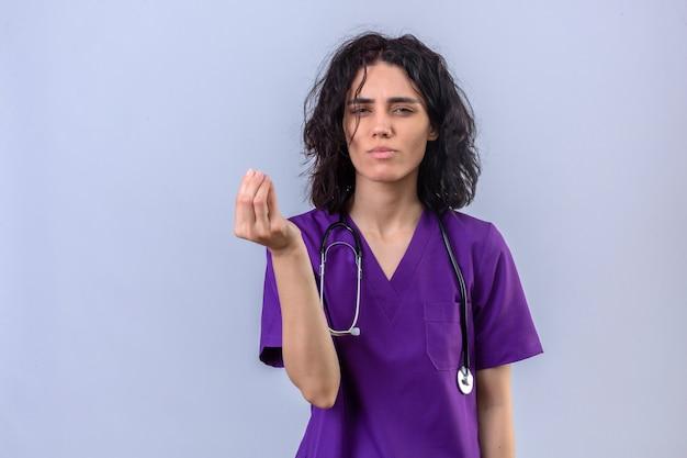의료 제복을 입은 여자 간호사와 격리 된 흰색에 서있는 급여 지불을 요구하는 손으로 돈 제스처를하고 청진 기