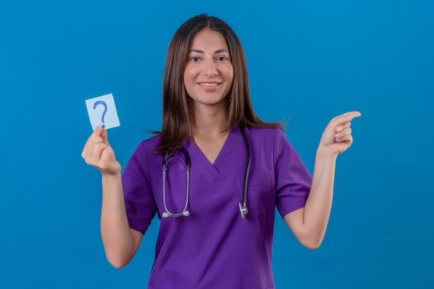 Woman nurse in medical uniform and with stethoscope holding reminder paper with question mark very happy pointing with hand and finger to the side standing on blue