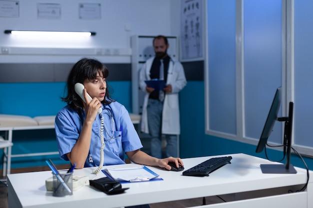 Woman nurse in uniform using landline phone for conversation