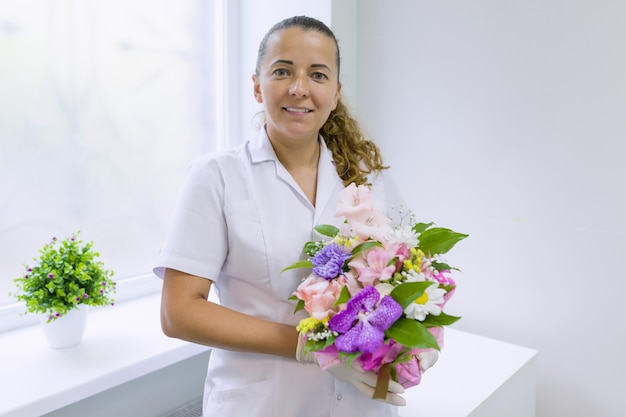 Woman nurse with bouquet of flowers