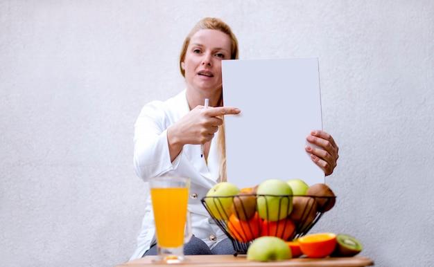 Женщина-диетолог, указывая пальцем на белый документ в своей клинике