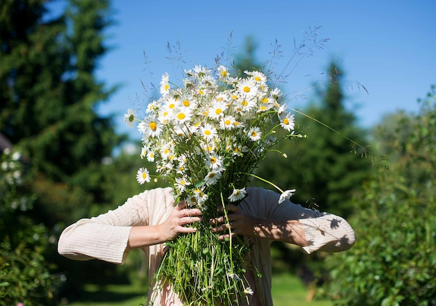 A woman obscures her face with a large bouquet of white daisy flowers