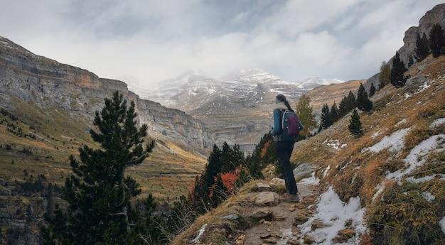 하이킹 코스의 경로에서 눈 덮인 산을 관찰하는 여자