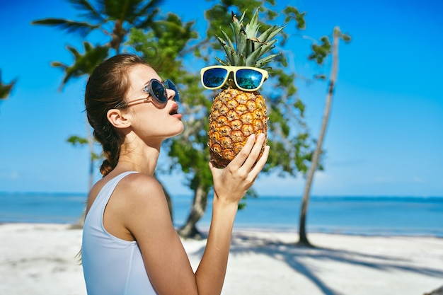 女性オーシャンパーム旅行、海とヤシの木、水着、メガネで休暇でポーズ美しいモデル
