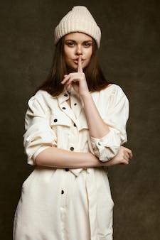 唇の近くで指を保持している女性の10月の帽子と暗いジャンプスーツ。