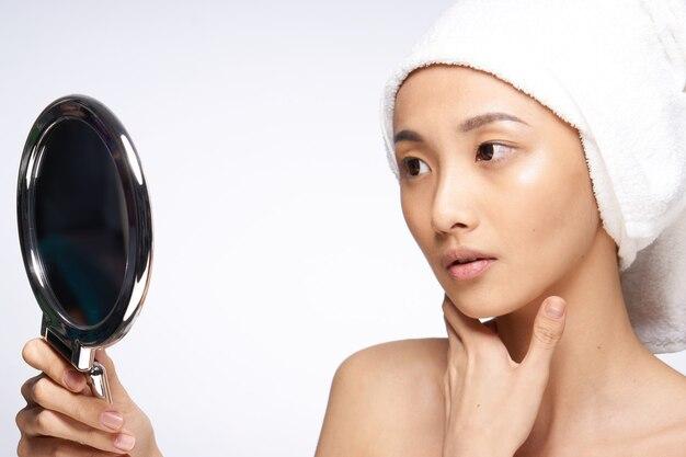 Женщина азиатской внешности смотрит в зеркало, уход за кожей, спа-процедуры