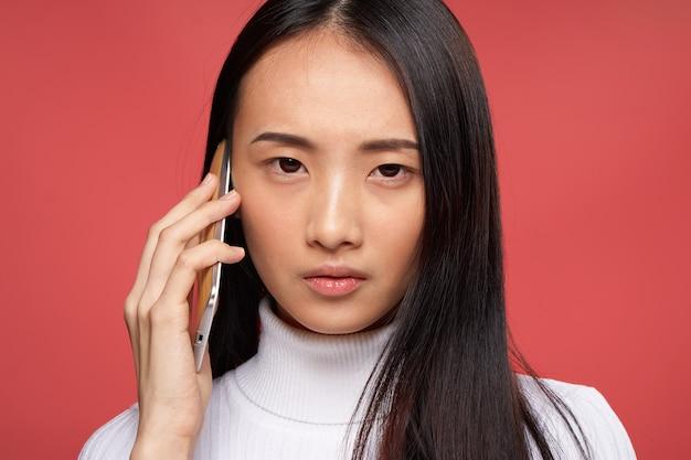 電話技術感情赤で話しているアジアの外観の女性