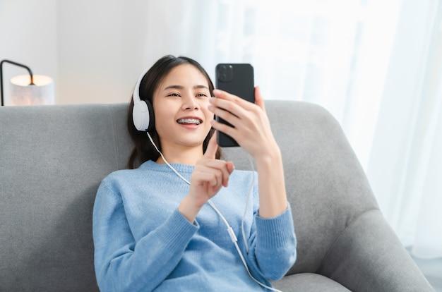 幸せな笑顔の女性は白いヘッドフォンから音楽を聴いています。