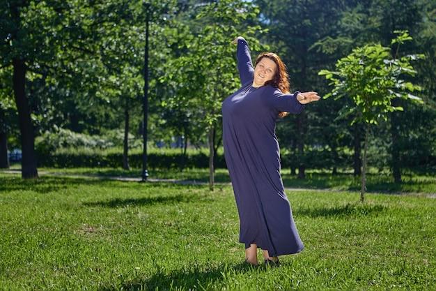 큰 체격의 여성이 공원의 잔디밭에서 춤을 추고 있다