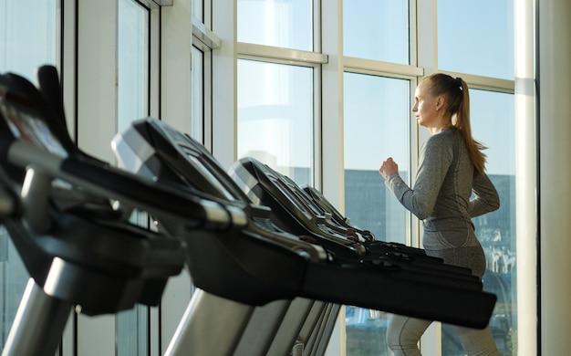 ジムでエクササイズ中年の女性。健康的な生活様式。エクササイズマシンでのトレーニング。