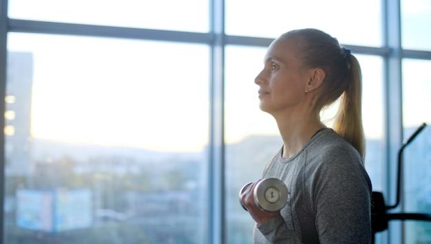 체육관에서 운동을하는 중간 나이의 여자. 건강한 라이프 스타일 운동 기계에 대한 교육.