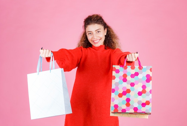 Donna che offre borse della spesa colorate alla sua amica.