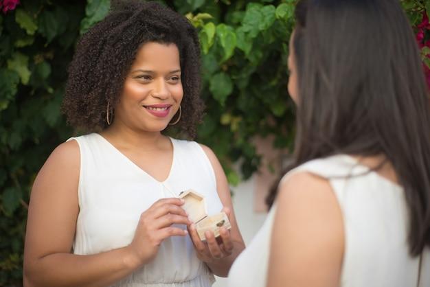 그녀의 여자 친구에게 약혼 반지를 제공하는 여자