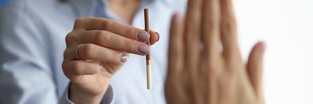 女性は否定的なジェスチャーをする男性にタバコを提供します。