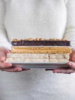 Женщина предлагает поднос с шоколадом и миндальной нугой. типичная испанская кухня.