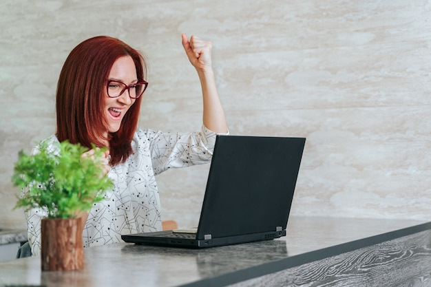 Woman at office desk with laptop feeling great on career horizon