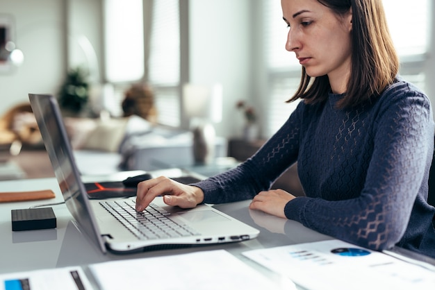 Woman in office at desk and working with laptop.