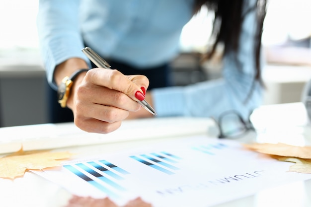 Woman in office holds a pen in her hand over chart